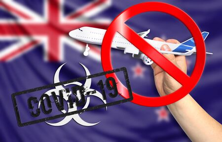 A new coronavirus disease called COVID - 19 with the flag of New Zealand. Contains the concept of a ban on air travel between countries. Фото со стока