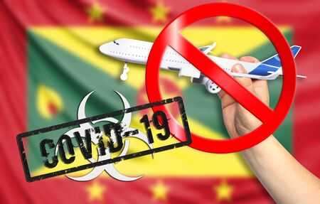 A new coronavirus disease called COVID - 19 with the flag of Grenada. Contains the concept of a ban on air travel between countries.