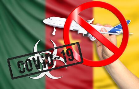 A new coronavirus disease called COVID - 19 with the flag of Cameroon. Contains the concept of a ban on air travel between countries. Фото со стока