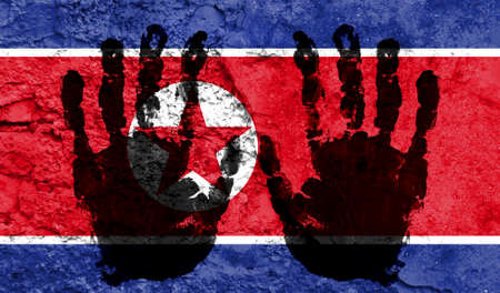 Handprints on the background of the flag of North Korea. Freedom of choice, corruption, and detention concept Archivio Fotografico