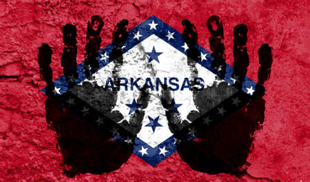 Handprints on the background of the flag of State of Arkansas. Freedom of choice, corruption, and detention concept