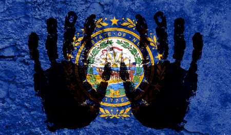 Handprints on the background of the flag of State of New Hampshire. Freedom of choice, corruption, and detention concept