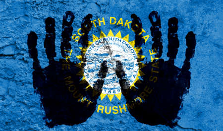 Handprints on the background of the flag of State of South Dakota. Freedom of choice, corruption, and detention concept Archivio Fotografico