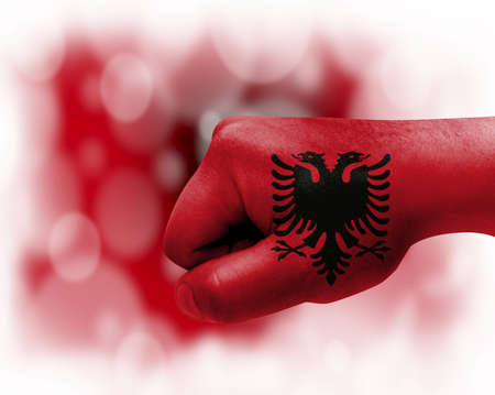 Flag of Albania painted on male fist, strength, power, concept of conflict. On a blurred background.