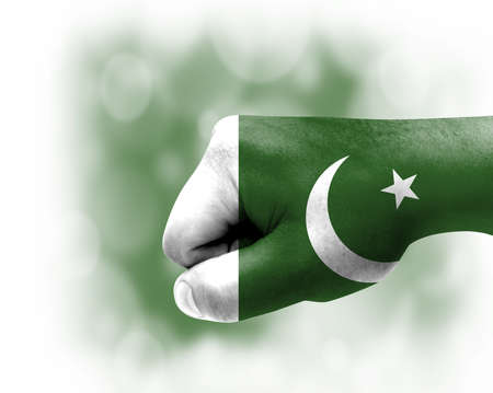Flag of Pakistan painted on male fist, strength, power, concept of conflict. On a blurred background.