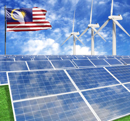 Solar panels on the background of a flagpole with the flag of Malaysia and Wind Turbine