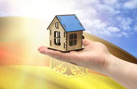 The concept of real estate mortgages, citizenship and accommodation, as well as investment in a future home. In hands holding a model of a wooden house against the background of the flag of Germany.