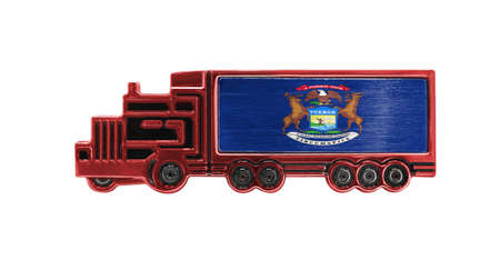 Toy truck with State of Michigan flag shown isolated on white background. The concept of cargo transportation between countries. Фото со стока