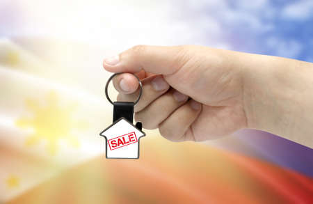 A man's hand holds a keychain in the form of a house with the inscription Sale on the background of the flag of Philippines. Property and real estate sale concept.