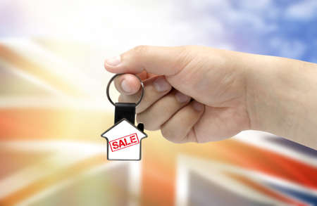 A man's hand holds a keychain in the form of a house with the inscription Sale on the background of the flag of United Kingdom. Property and real estate sale concept.