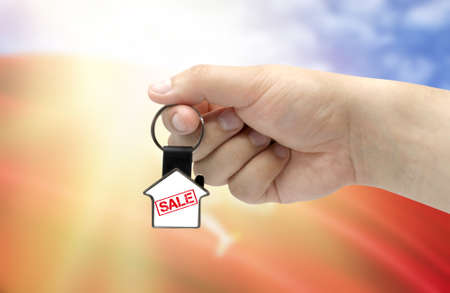 A man's hand holds a keychain in the form of a house with the inscription Sale on the background of the flag of Isle Of Man. Property and real estate sale concept. Stockfoto
