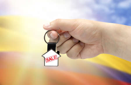 A man's hand holds a keychain in the form of a house with the inscription Sale on the background of the flag of Colombia. Property and real estate sale concept.
