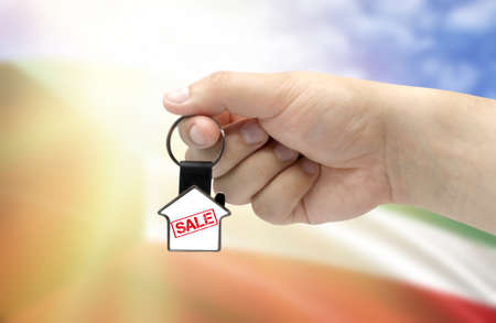 A man's hand holds a keychain in the form of a house with the inscription Sale on the background of the flag of Kuwait. Property and real estate sale concept.