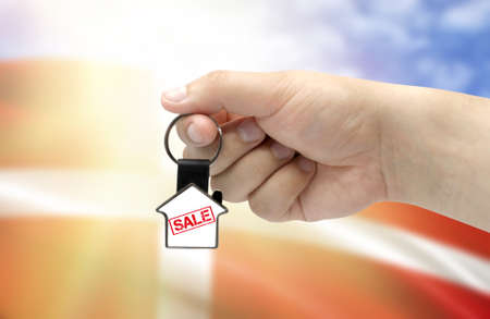 A man's hand holds a keychain in the form of a house with the inscription Sale on the background of the flag of Denmark. Property and real estate sale concept. Stockfoto