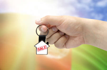 A man's hand holds a keychain in the form of a house with the inscription Sale on the background of the flag of Afghanistan. Property and real estate sale concept.