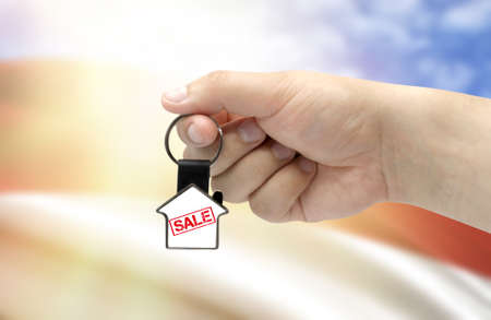 A man's hand holds a keychain in the form of a house with the inscription Sale on the background of the flag of Indonesia. Property and real estate sale concept.