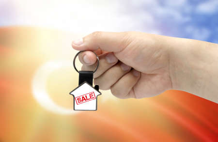 A man's hand holds a keychain in the form of a house with the inscription Sale on the background of the flag of Turkey. Property and real estate sale concept.
