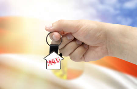 A man's hand holds a keychain in the form of a house with the inscription Sale on the background of the flag of Salzburg. Property and real estate sale concept.