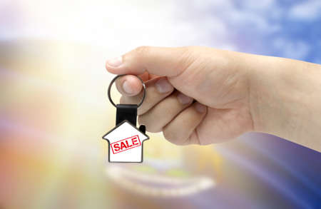 A man's hand holds a keychain in the form of a house with the inscription Sale on the background of the flag of State of Michigan. Property and real estate sale concept.