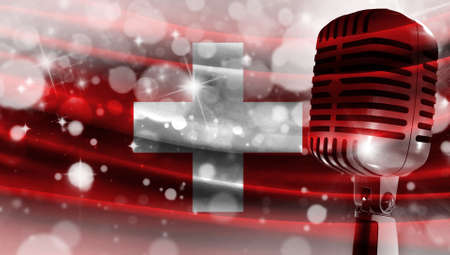 Microphone on a background of a blurry flag Switzerland close-up, a design concept for your layout with a good place for text and images.