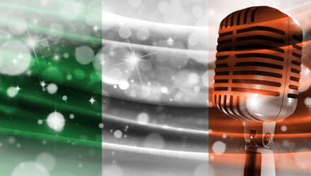 Microphone on a background of a blurry flag Ireland close-up, a design concept for your layout with a good place for text and images.