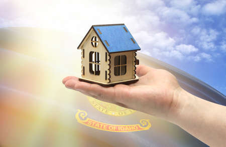 The concept of real estate mortgages, citizenship and accommodation. In hands holding a model of a wooden house against the background of the flag of State of Idaho.