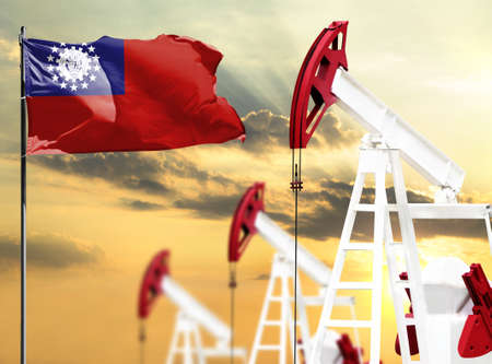 Oil rigs against the backdrop of the colorful sky and a flagpole with the flag of Myanmar Burma. The concept of oil production, minerals, development of new deposits. 스톡 콘텐츠