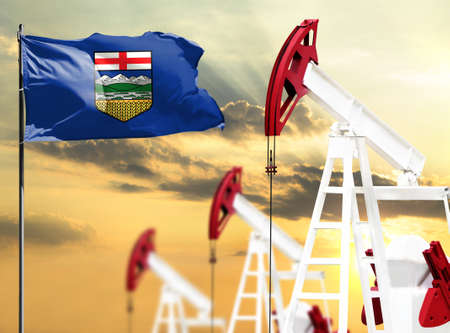 Oil rigs against the backdrop of the colorful sky and a flagpole with the flag of Alberta. The concept of oil production, minerals, development of new deposits.