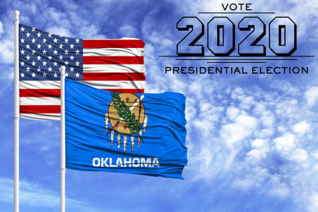 US elections in November 2020, against a blue sky, two flagpoles with the flag of America and the State of Oklahoma. 写真素材