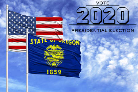 US elections in November 2020, against a blue sky, two flagpoles with the flag of America and the State of Oregon.