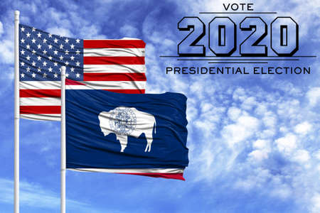 US elections in November 2020, against a blue sky, two flagpoles with the flag of America and the State of Wyoming.