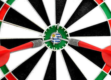 Close-up of a dart board with an imprinted flag of Uruguay in the center. The concept of achieving goals.