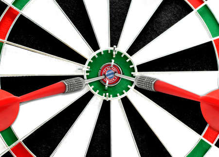 Close-up of a dart board with an imprinted flag of FC Bayern Munich in the center. The concept of achieving goals.