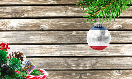 Concept of New Year and Christmas, on a wooden background, Christmas tree branches and a Christmas toy with the flag of Crimea.