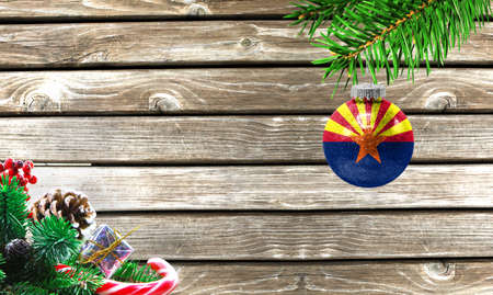 Concept of New Year and Christmas, on a wooden background, Christmas tree branches and a Christmas toy with the flag State of Arizona.