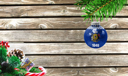 Concept of New Year and Christmas, on a wooden background, Christmas tree branches and a Christmas toy with the flag State of Wisconsin.