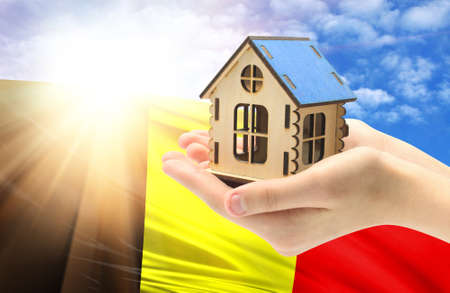 The concept of real estate mortgages, citizenship and accommodation, as well as investment in a future home. In hands holding a model of a wooden house against the background of the flag of Belgium.