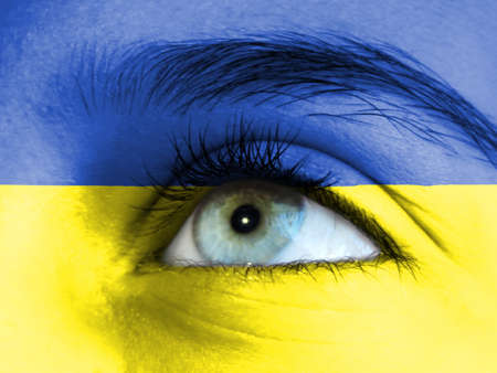Close up view of a young girl. The flag of Ukraine is painted on the girl face.