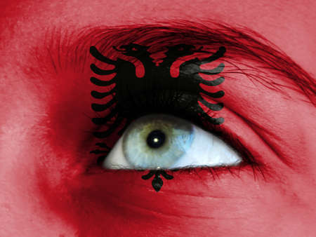 Close up view of a young girl. The flag of Albania is painted on the girl face.
