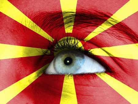 Close up view of a young girl. The flag of Macedonia is painted on the girl face.