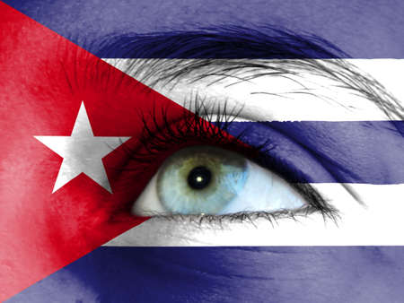 Close up view of a young girl. The flag of Cuba is painted on the girl face.