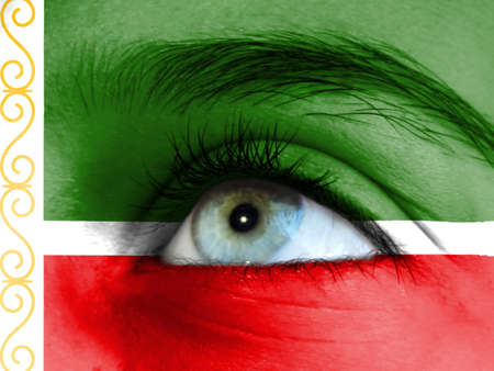 Close up view of a young girl. The flag of Chechen Republic is painted on the girl face.