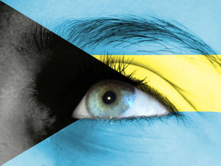 Close up view of a young girl. The flag of Bahamas is painted on the girl face.