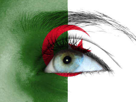 Close up view of a young girl. The flag of Algeria is painted on the girl face.