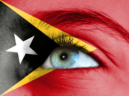 Close up view of a young girl. The flag of East Timor is painted on the girl face.