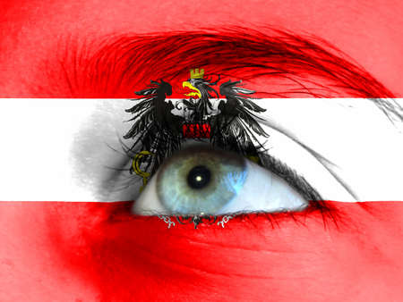 Close up view of a young girl. The flag of Austria is painted on the girl face.