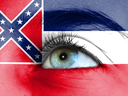 Close up view of a young girl. The flag State of Mississippi is painted on the girl face.
