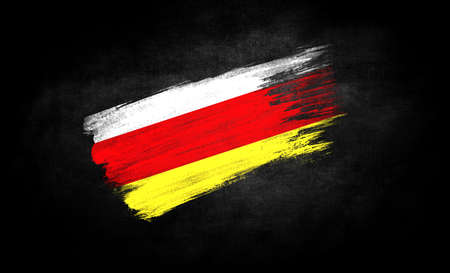smear of paint in the form of the flag of North Ossetia close-up on a black background Banco de Imagens