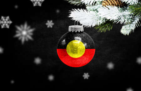 Happy new Year 2021, flag of Australian Aboriginal on a christmas toy, decorations isolated on dark background. Creative christmas concept.