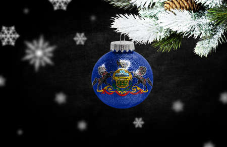 Happy new Year 2021, flag State of Pennsylvania on a christmas toy, decorations isolated on dark background. Creative christmas concept.